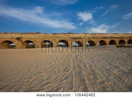 Ancient Aqueduct Between Sand And Skies
