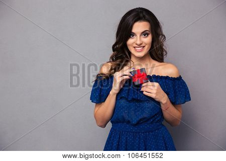 Portrait of a smiling young woman holding jewelry gift box over gray background