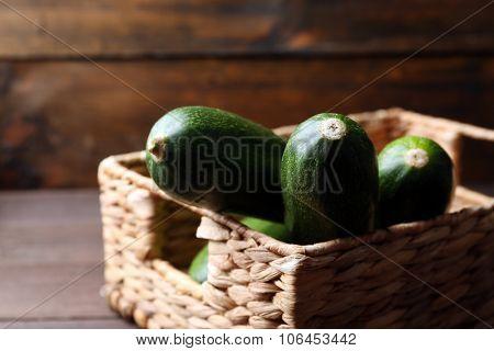 Fresh zucchini in wicker basket on wooden background