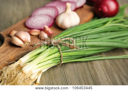 Red onions circles, green onion with garlic on board against wooden background