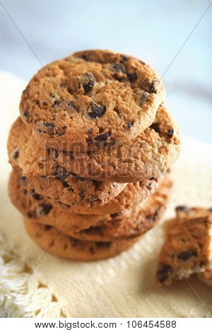 Cookies with chocolate crumbs on white napkin against blurred background, close up