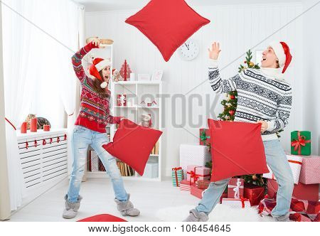 Happy Loving Couple Laughing And Fighting On Pillows On Christmas