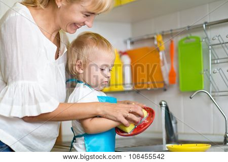 Kid boy and mother washing dishes - having fun together in the kitchen