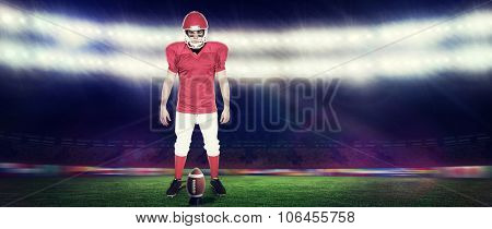 Serious american football player looking at camera against rugby stadium