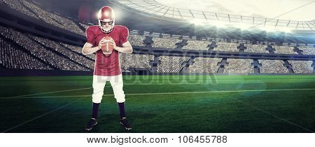 American football player holding a ball against rugby stadium