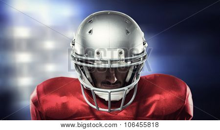 Close-up of serious American football player in red jersey looking down against white lights glowing