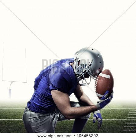 Upset American football player with ball against american football posts