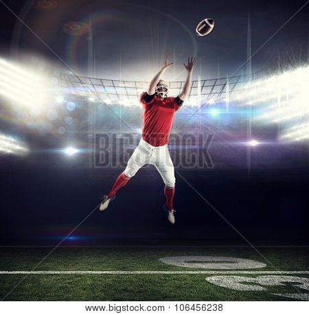 American football player trying to catch football against american football arena