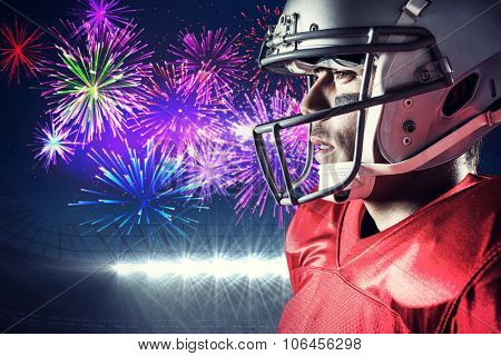 Side view of sportsman wearing helmet against fireworks exploding over football stadium