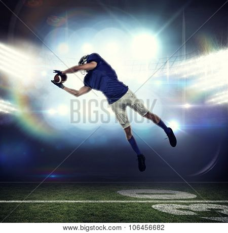 American football player catching ball in mid-air against american football arena