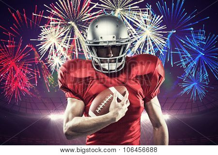Portrait of confident American football player in red jersey holding ball against fireworks exploding over football stadium