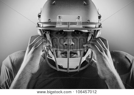 Close-up portrait of American football player holding helmet against black background