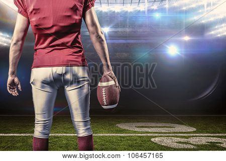 Mid section of American football player with ball against american football arena
