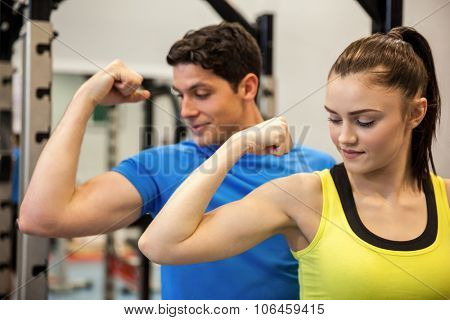 Happy couple showing off their biceps at the gym