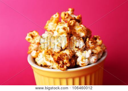 Sweet caramel popcorn on pink background