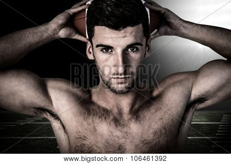 Portrait of a man holding ball over his head against spotlight