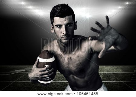 Shirtless rugby player defending against spotlight