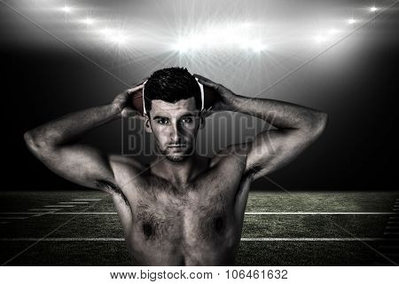 Portrait of a shirtless man holding ball over head against spotlight