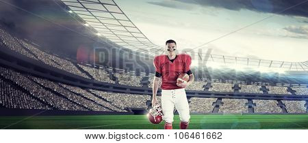 Portrait of american football player walking and holding football and helmet against rugby stadium