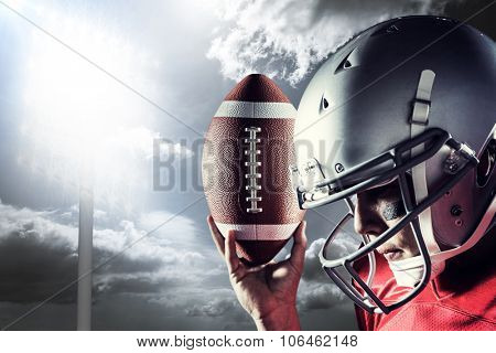 Sportsman looking down while holding American football against spotlight in sky