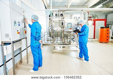 Two pharmaceutical male workers operating water preparation production line at pharmacy industry manufacture factory using notebook computer