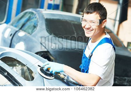 smiling auto mechanic worker sanding bumper car at automobile repair and renew service station shop by power polishing machine