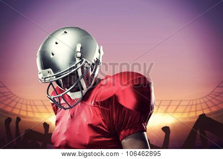 American football player looking down against football stadium with cheering crowd