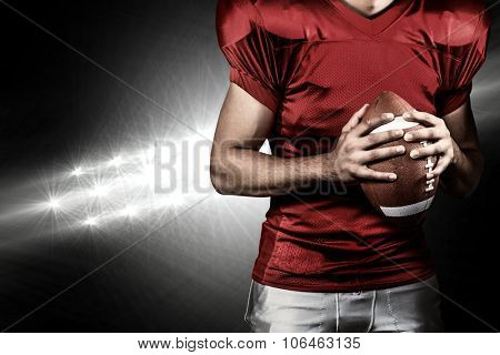 Mid section of American football player holding ball against spotlights