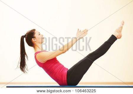 fitness, sport, training, gym and wellness. Woman doing stretching excercises on the fitness mat in gym