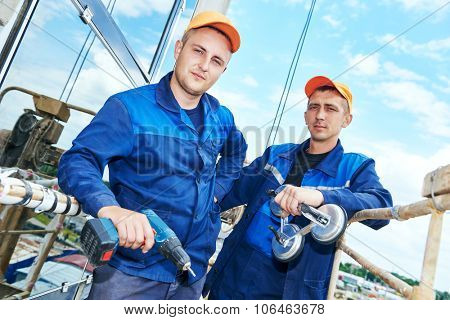 Portrait of two builders worker with glass suction plate and hand drill in front of facing wall of business building