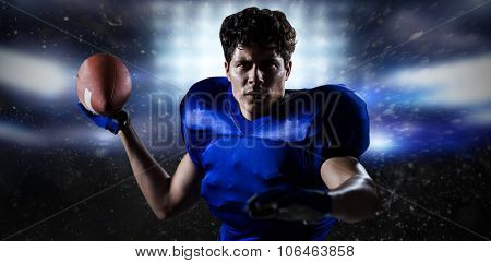 Portrait of sportsman throwing football against sports pitch