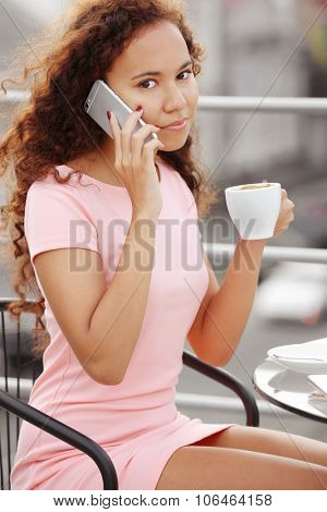 Close up portrait of pretty young woman speaking by cellphone and drinking coffee