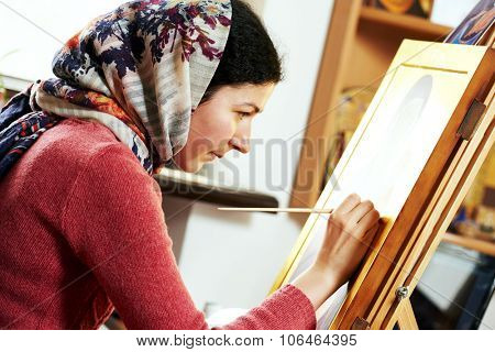 Iconography. Religious icon painter woman paints a new icon with brush at workshop