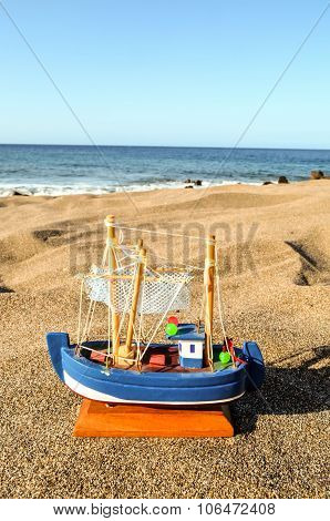 Toy Boat on the Sand Beach