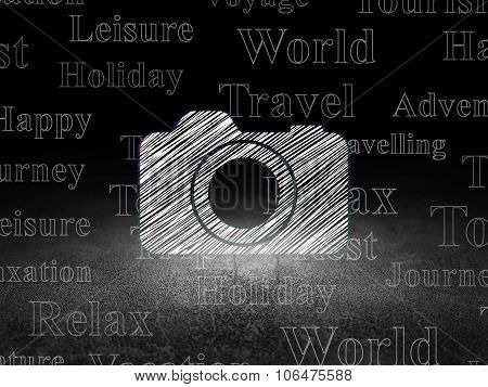 Travel concept: Photo Camera in grunge dark room