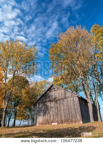 Old wooden barn surrounded by trees in fall colors