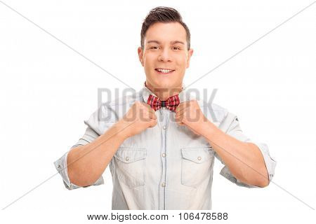 Studio shot of a young man adjusting his bow-tie and looking at the camera isolated on white background