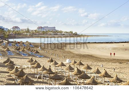 Straw Umbrellas And Loungers On The Playa De Las Americas, Tenerife