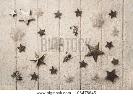 Nostalgic white silver and sepia christmas decoration with stars on old wooden background.