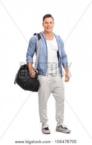 Full length portrait of a young sportsman carrying a sports bag over his shoulder and looking at the camera isolated on white background