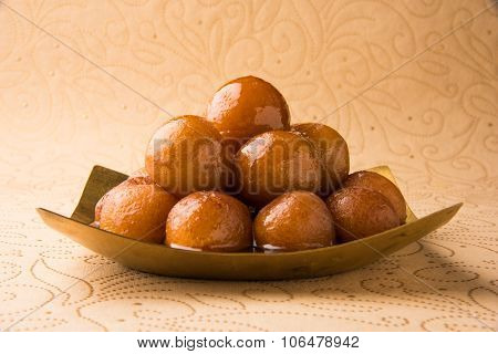 indian sweet gulab jamun in square shape brass plate, closeup and front view on cream paper with flo