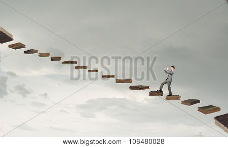 Young businessman in black hat walking on book steps and playing flute