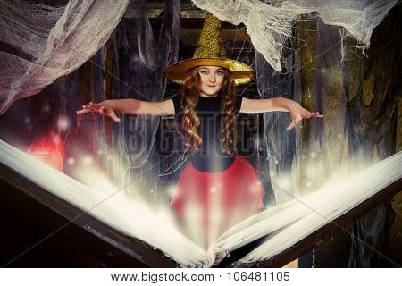 Beautiful little girl in a costume of witch in a wizarding lair. Halloween party. Halloween decorations.