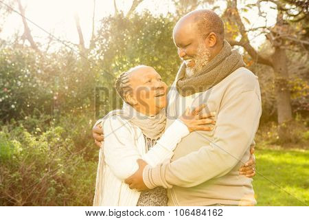 Happy peaceful senior couple embracing in parkland