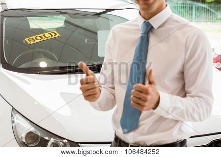 Smiling businessman standing while giving thumbs up at new car showroom