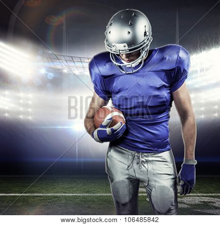 American football player looking down while holding ball against american football arena