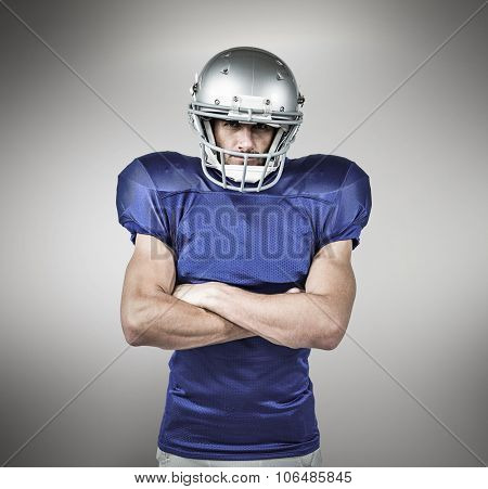 Portrait of American football player with arms crossed against grey vignette