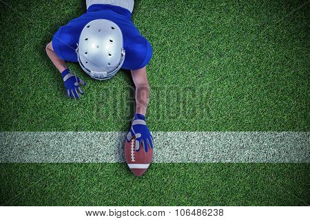 American football player reaching towards ball against pitch with line