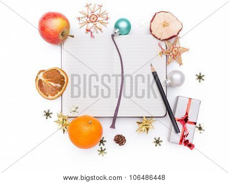 A Notebook And A Pencil With Christmas Decoration Around It