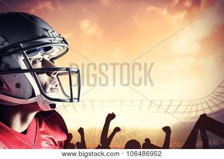 American footballer looking up against football stadium with cheering crowd